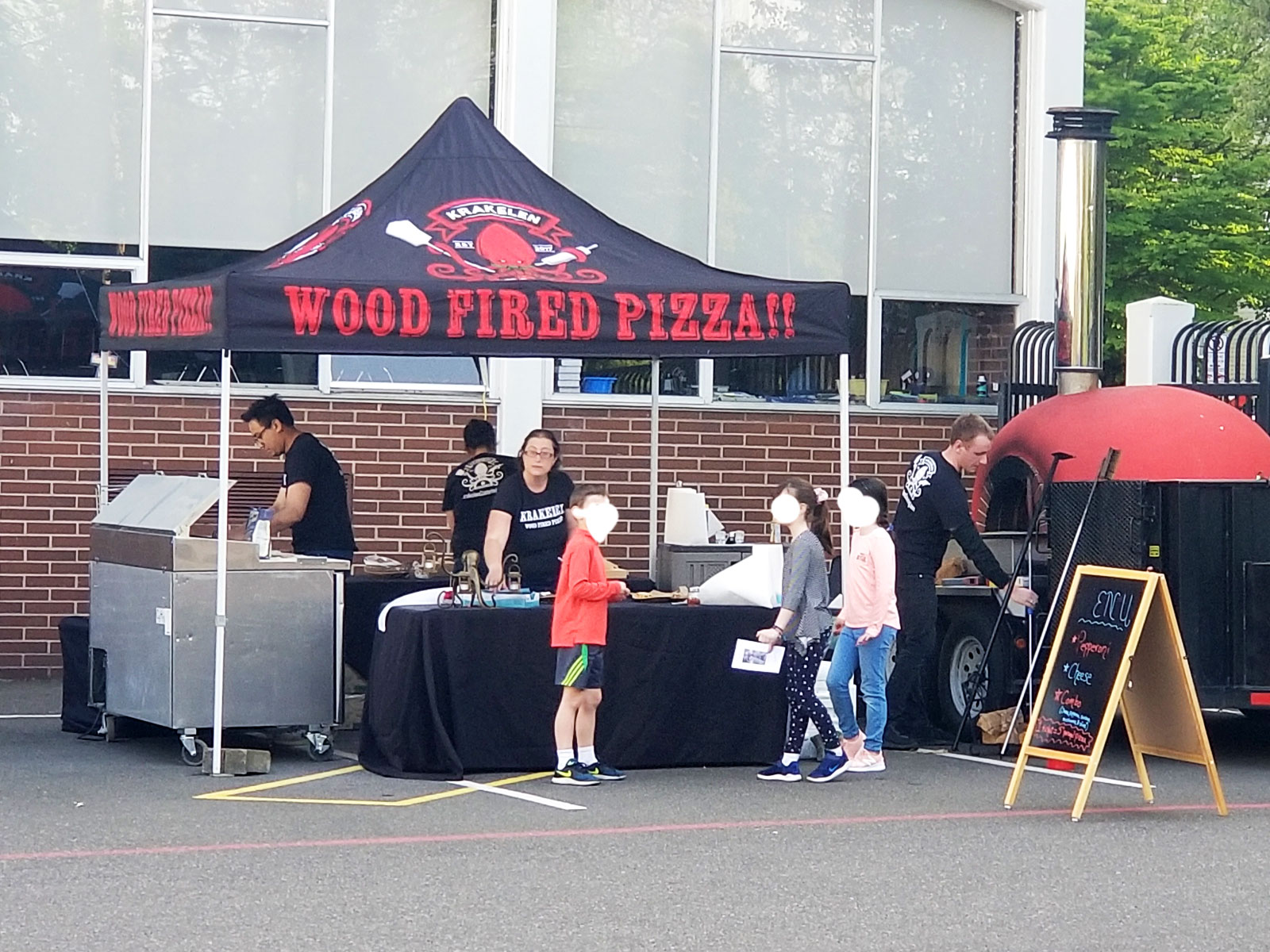 A Krakelen pizza food tent with staff using a grill and wood oven, at the Wilsonville campus