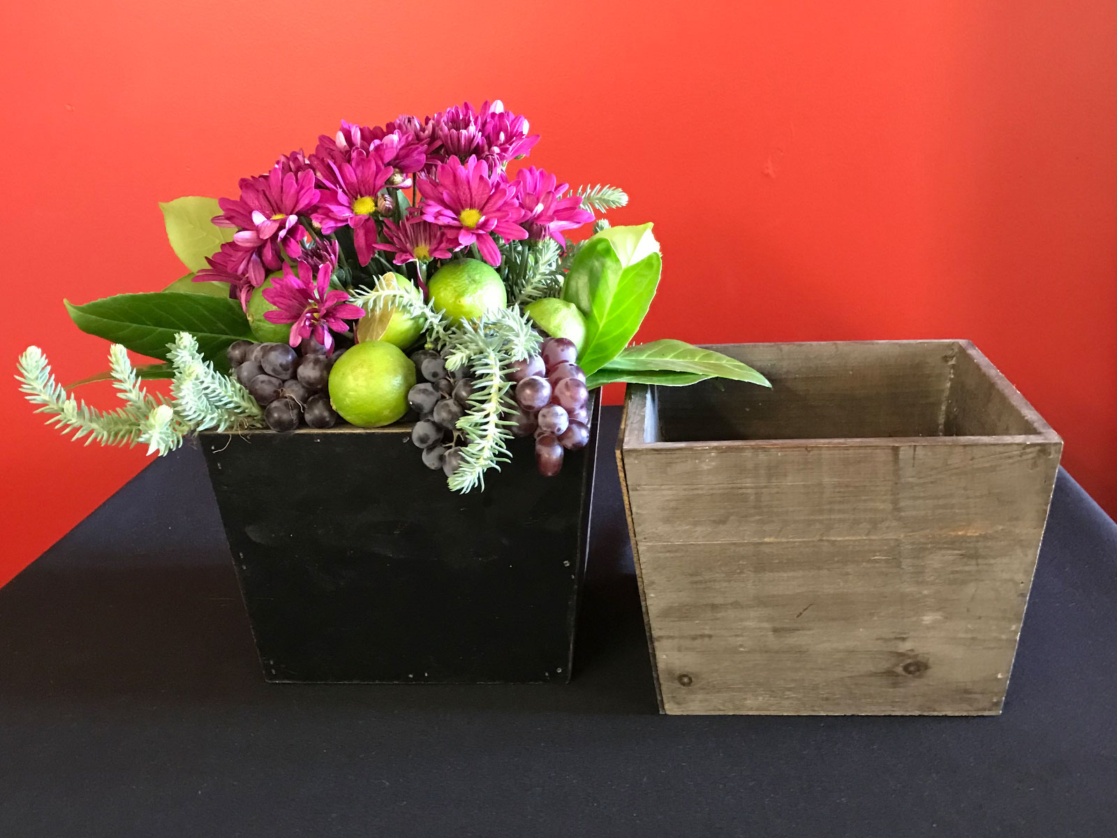 Purple flowers with green leaves, limes and grapes set in a grey box