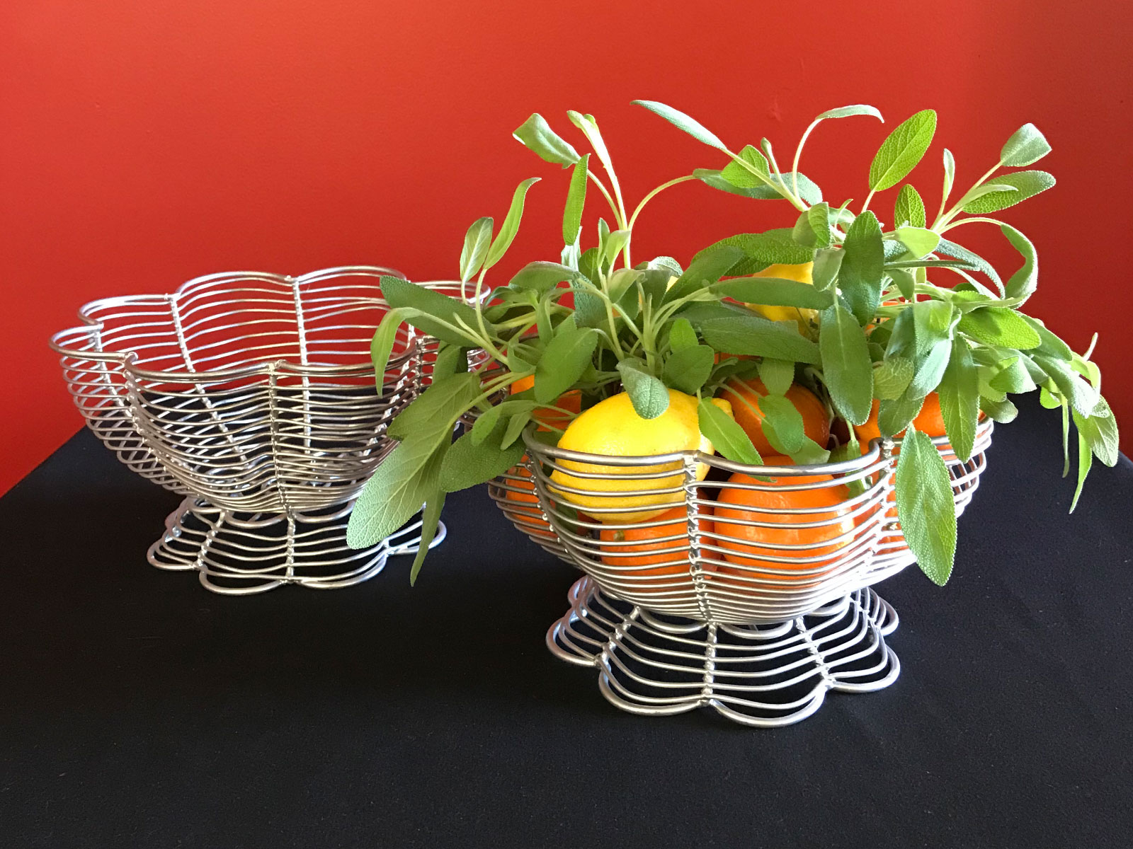 Several wax fruit centerpieces including oranges and lemons in white baskets