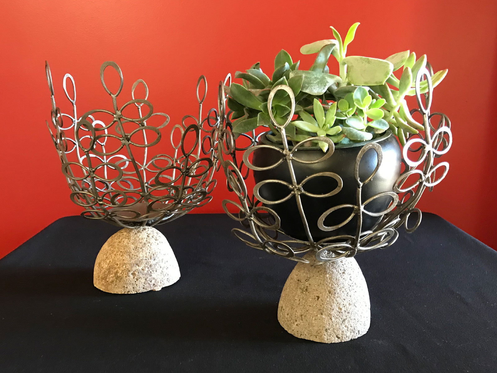 A flower pot of small green-leaf plants set in a designed metal cradle on top of decorative stone