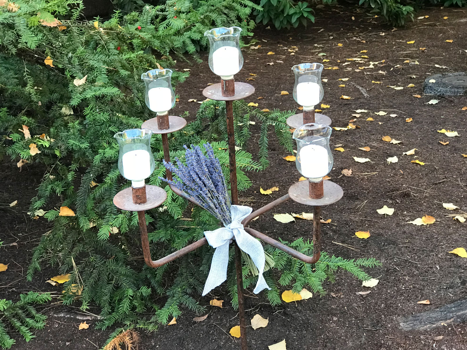 A five-candle metal centerpiece, set in the outside garden of the Oregon City campus