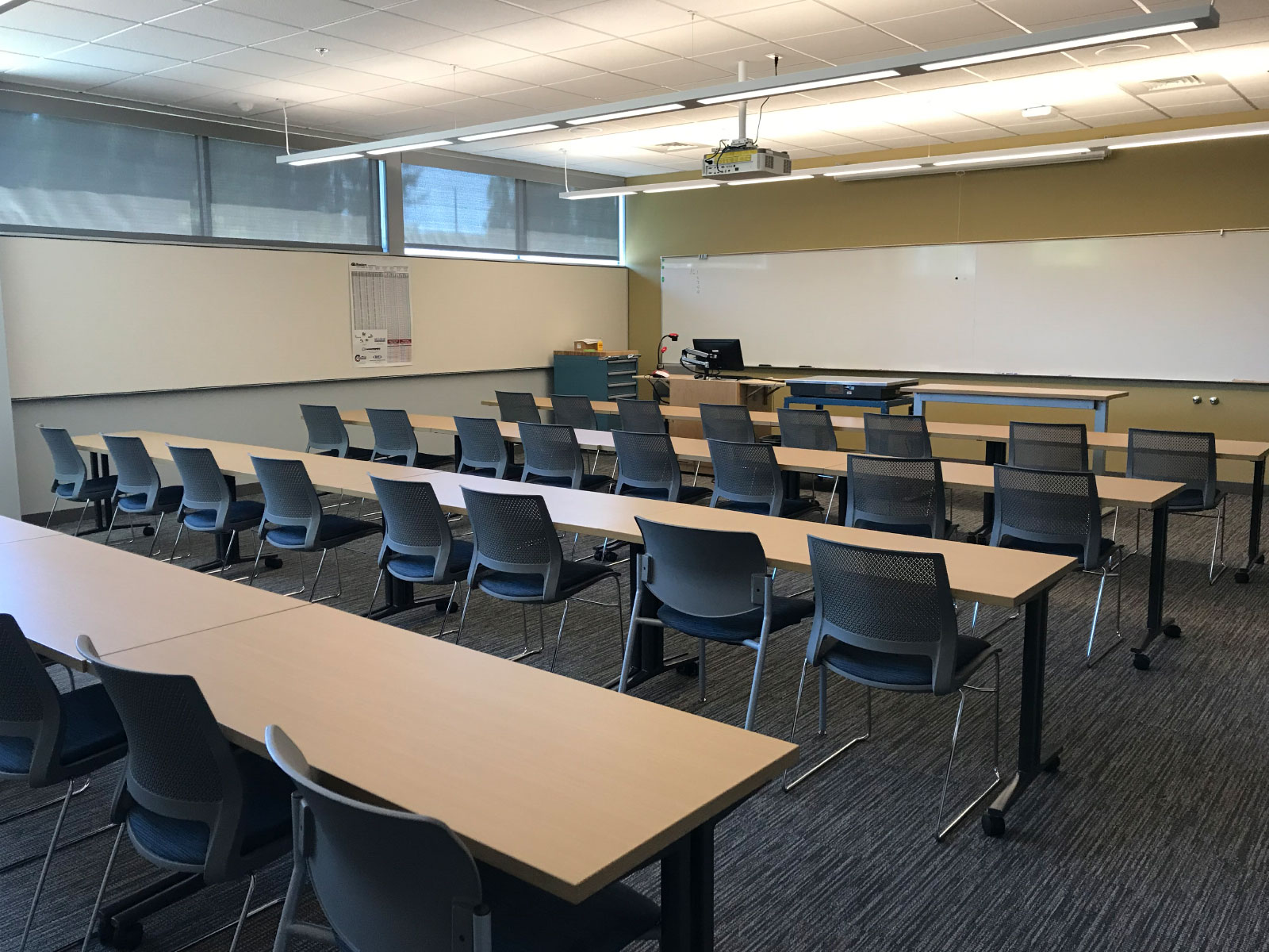 Several rows of tables and chairs in a classroom with a room-wide whiteboard in the Oregon City campus' Industrial Technology Center
