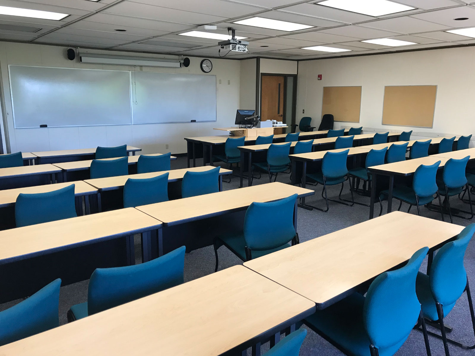 Rows of tables with blue chairs in a classroom with a large whiteboard and projector