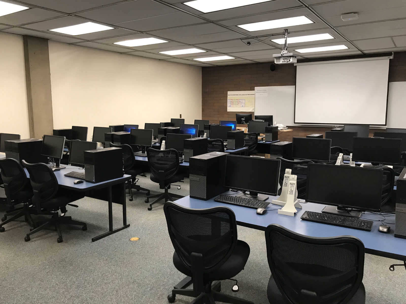 Rows of tables with computers and comfortable, ergonomic chairs in front of a projector screen in a computer lab on the Oregon City campus
