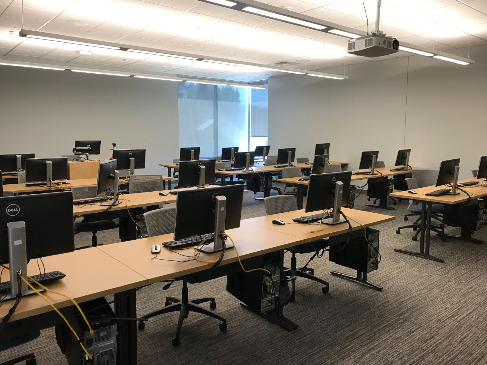 Rows of tables with silver chairs and computers in a windowed computer lab on the Oregon City campus