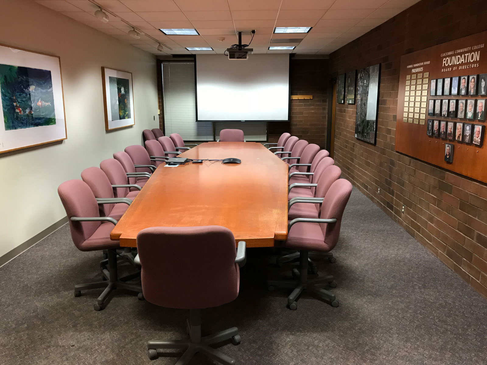 A long, skinny table with many chairs in front of a projector, surrounded by paintings and awards, in a conference room at the Oregon City campus