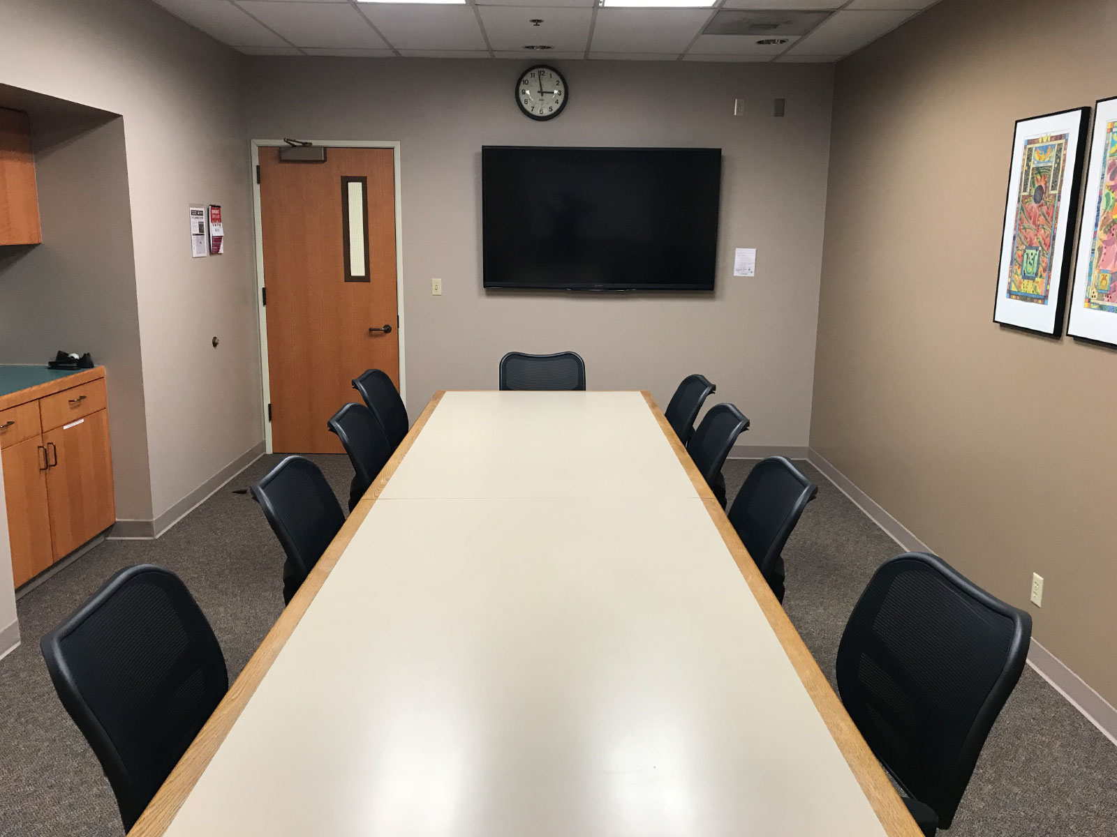 A long table with several chairs in a conference room with a TV display on the Oregon City campus