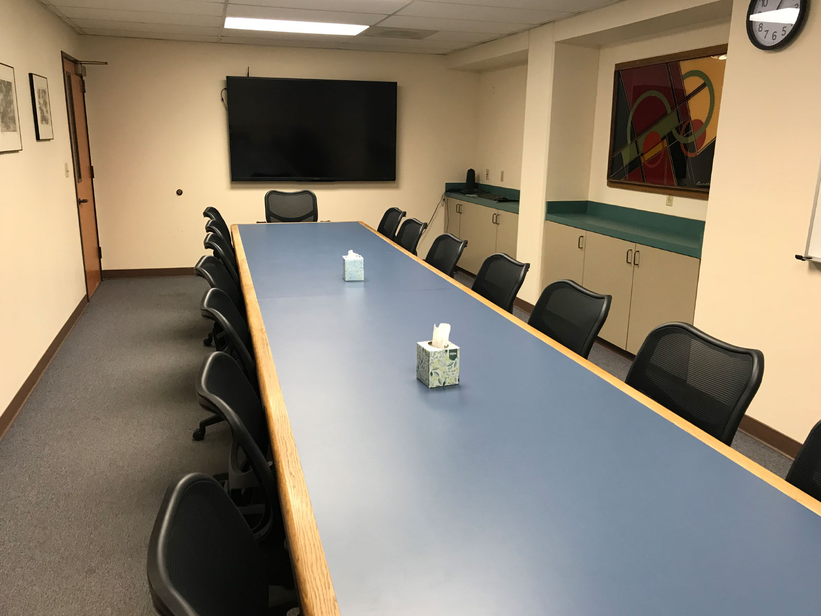 A long, blue table with several chairs in a conference room with a TV display on the Oregon City campus