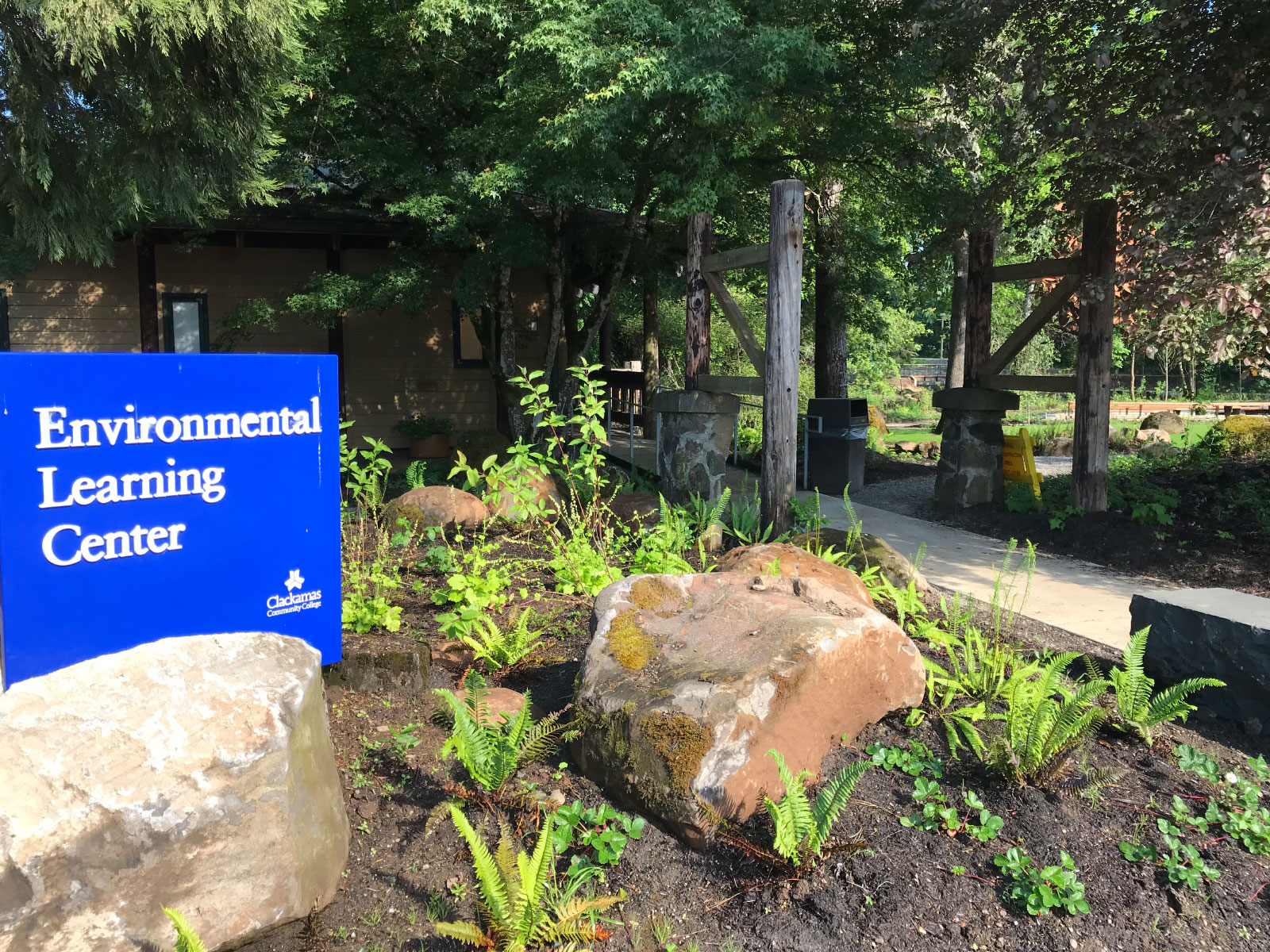 The Environmental Learning Center's blue entrance sign, surrounded by rocks and greenery, just outside Lakeside Hall, at the Oregon City campus