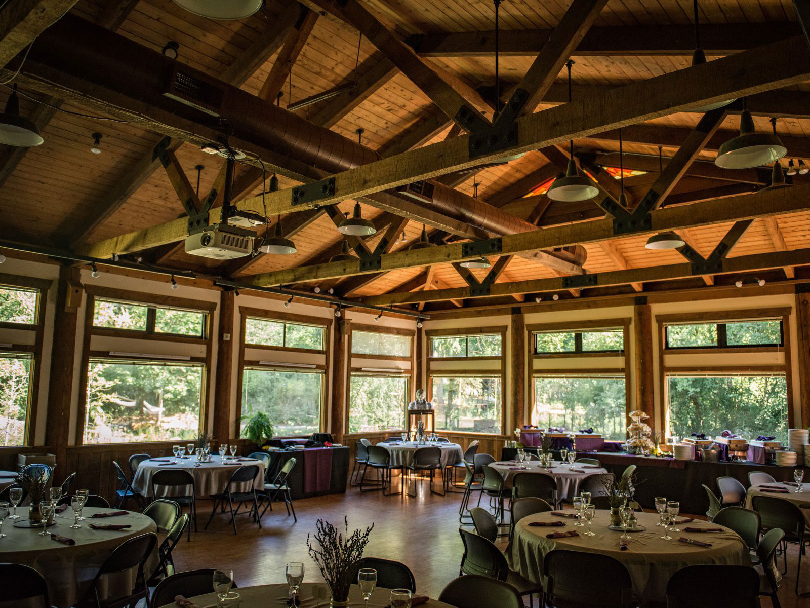 The inside of the Environmental Learning Center's Lakeside Hall, featuring decorated tables, glassware and catered drinks