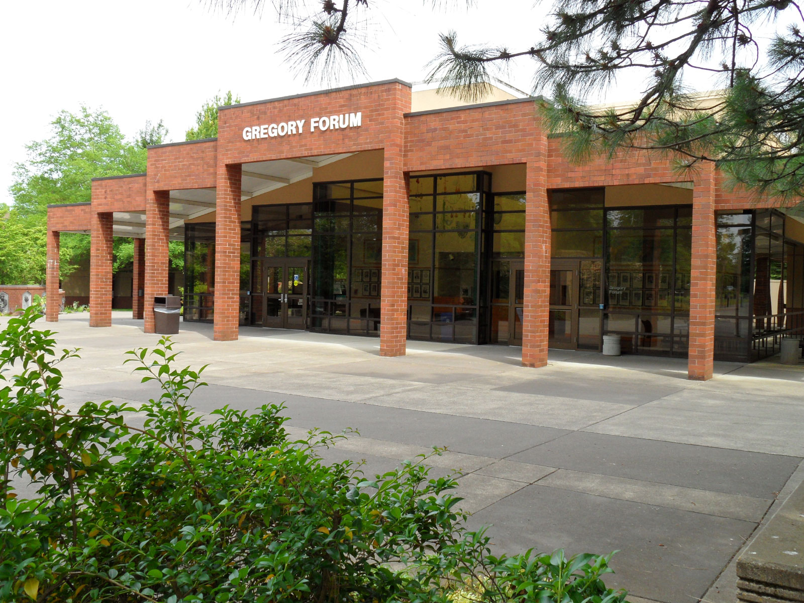 The entrance to Gregory Forum, featuring brick arches, full walls of glass and leafy surroundings at the Oregon City campus