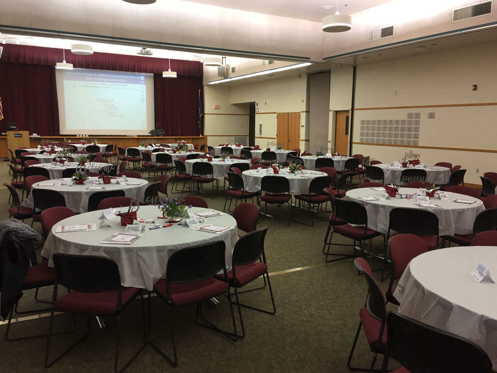 Many tables with red chairs, table centerpieces and silverware with a projector screen at the front of the room