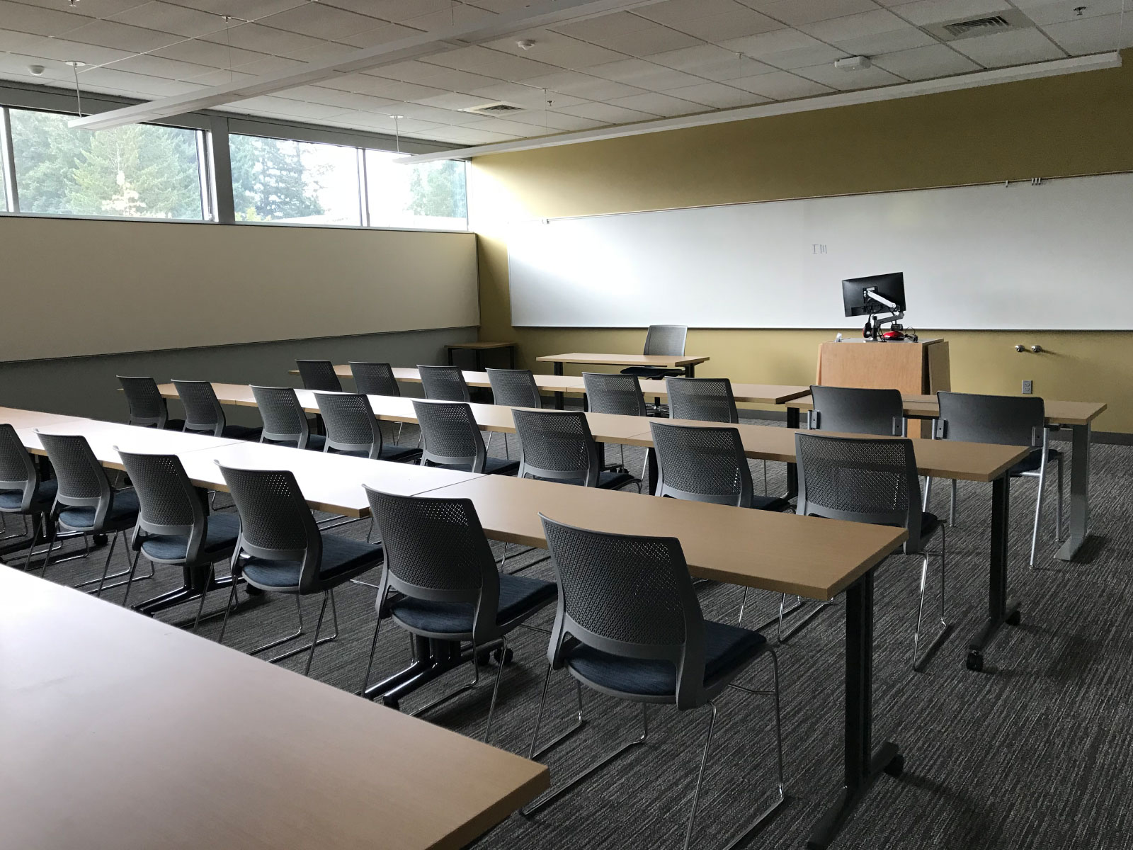 One of the Industrial Technology Center's many classrooms, featuring rows of chairs and table with a podium and room-wide whiteboard