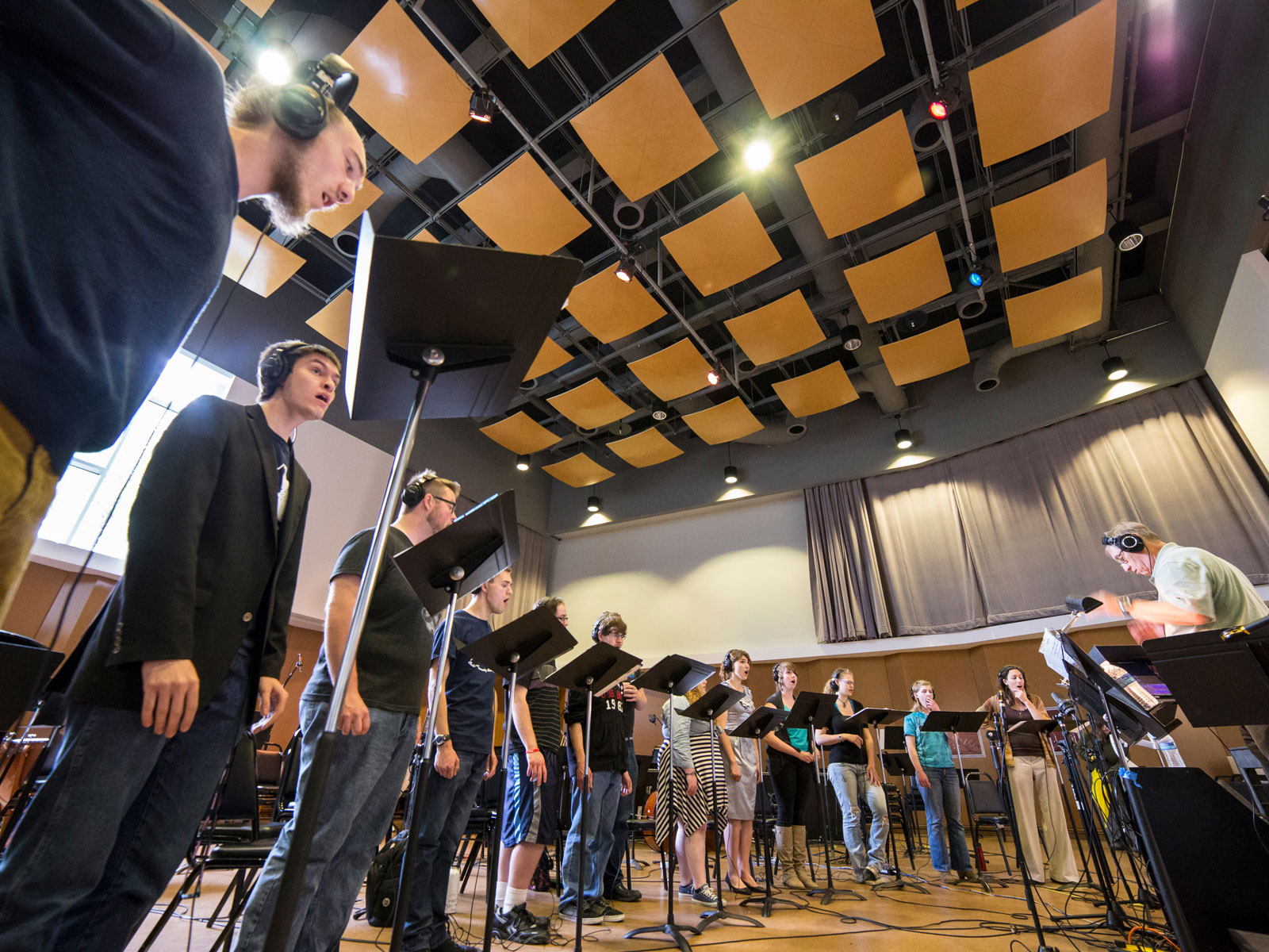 Singers in the recording hall with instructor and several music stands at the Niemery Center