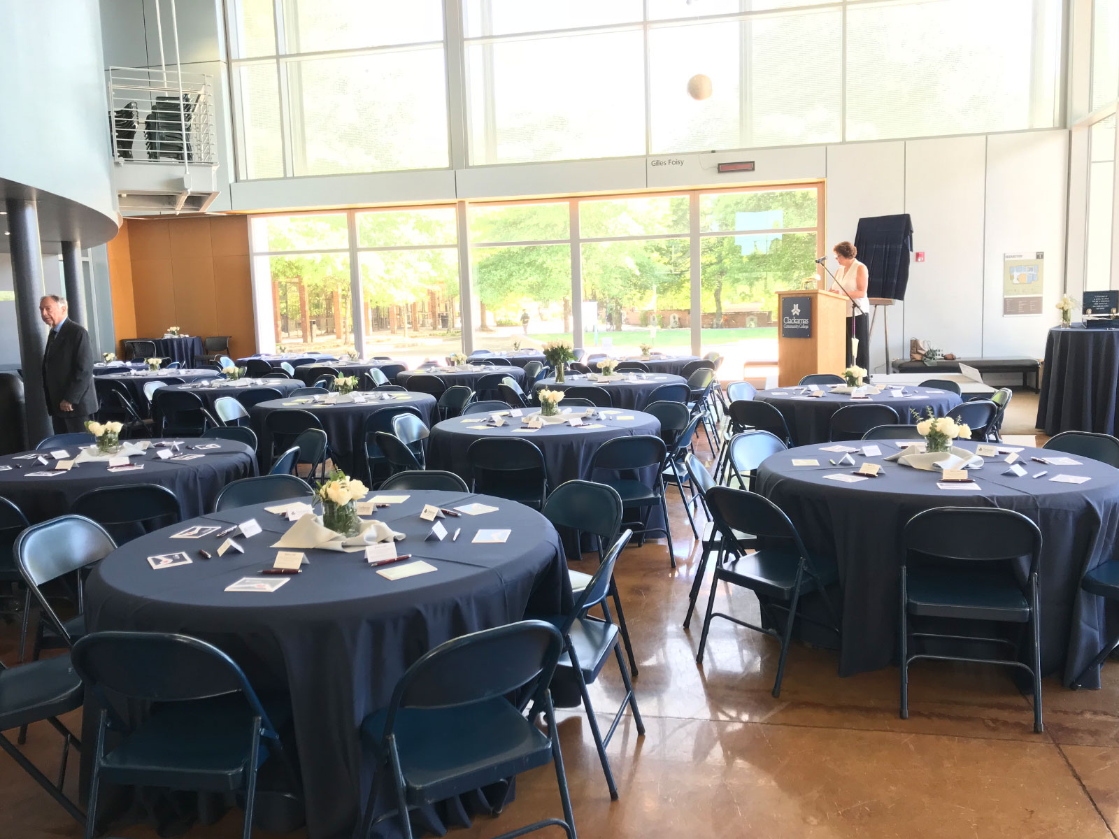 Decorated tables and podium for an event in Niemeyer Center's open lobby at the Oregon CIty campus