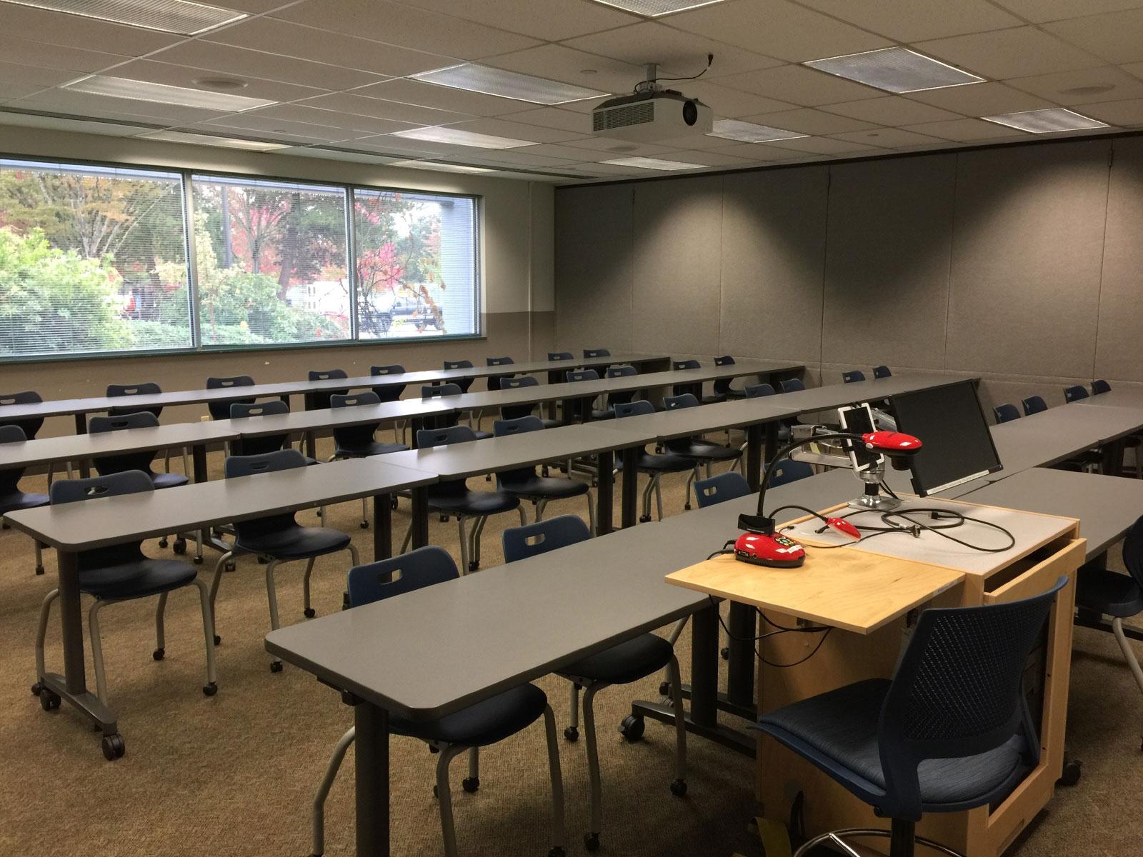 Rows of chairs and tables in front of a podium and projector in classroom W112 on the WIlsonville campus