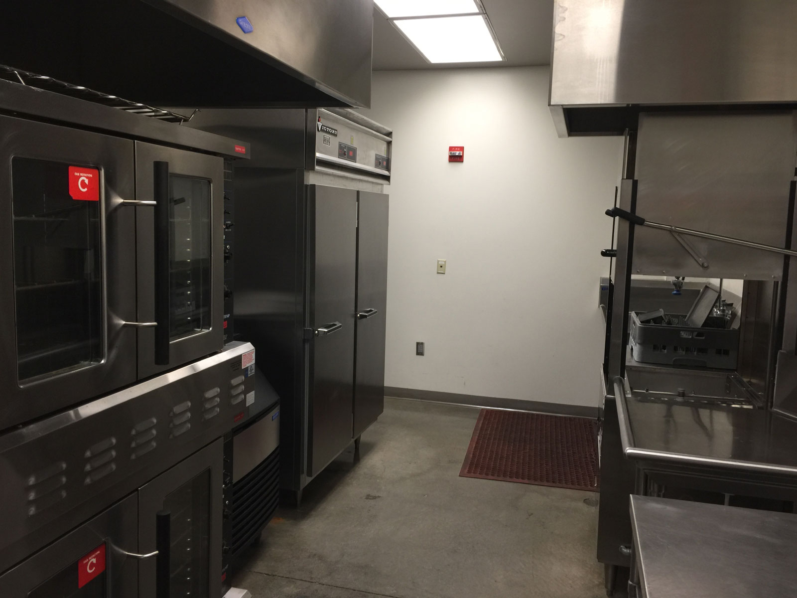 The back area of the Wilsonville campus kitchen area with a refridgerator, dishwasher and heating units