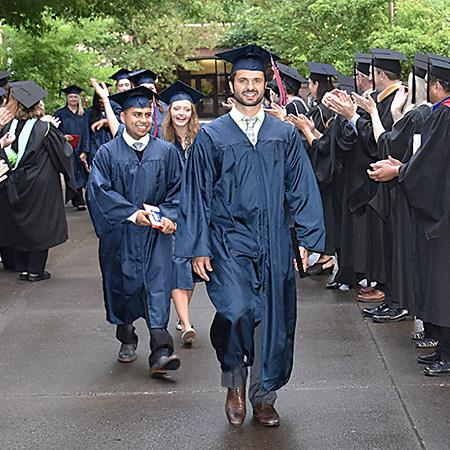 graduate in cap and gown walks through line of applauding faculty
